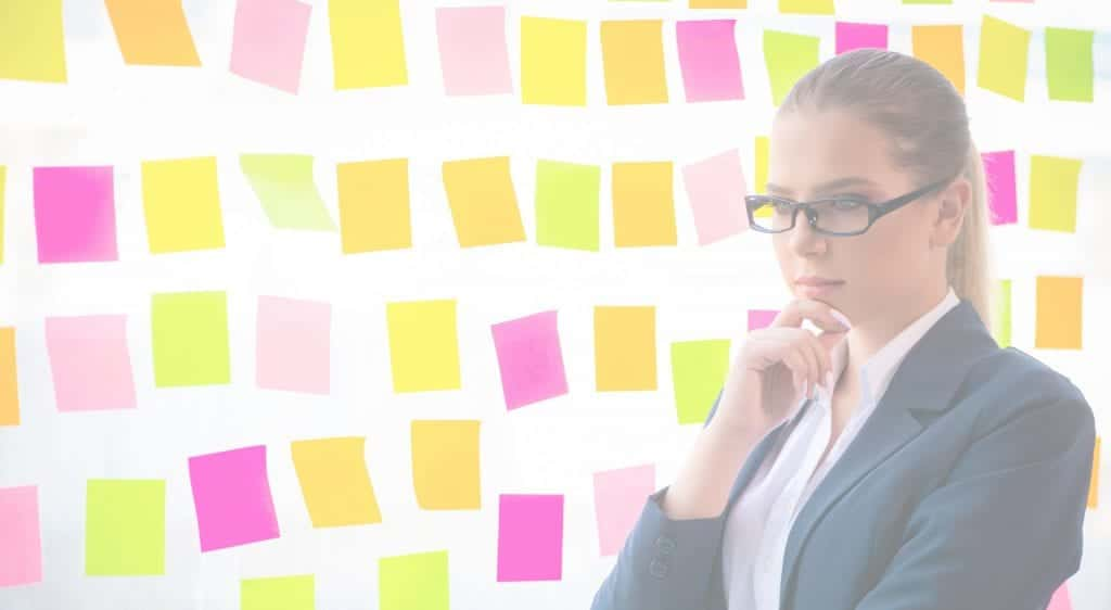 The Product Backlog is Ordered to Maximize Value - Businesswoman Thinking in Front of Glass Wall of Sticky Notes Cropped Filtered Photo