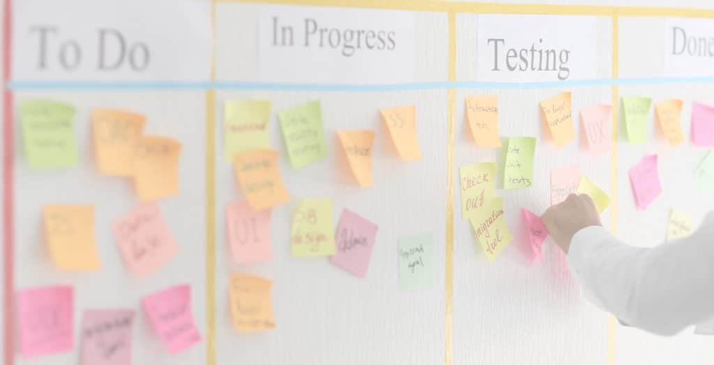 Product Backlog Items Are Features or Functions - Man Moving Sticky to Testing Section of Scrum Task Board Photo