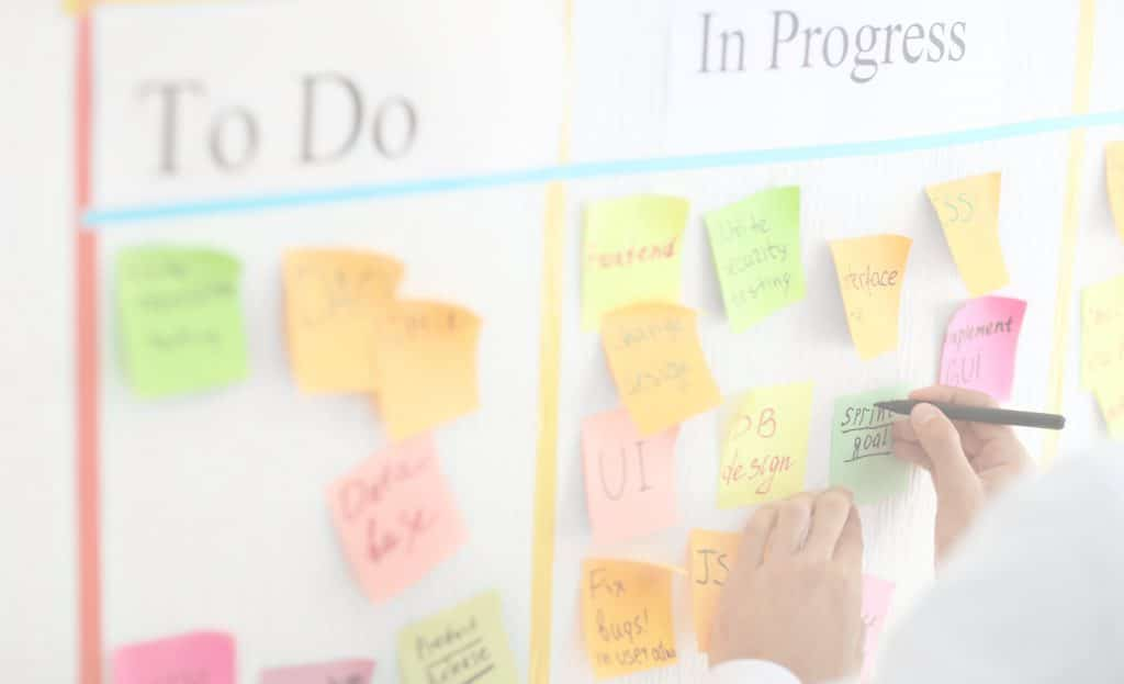 Product Backlog Items are written as User Stories - Man Writing on Sticky Note Attached to Scrum Task Board Photo
